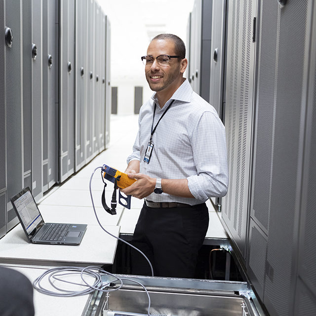 Two men using a HP Z Book 14″ while working in a data center.
